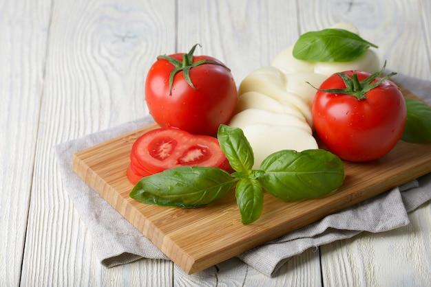 Mozzarella und tomate mit basilikumblättern auf einer weißen holzoberfläche