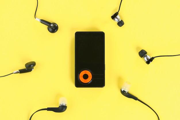 Mp3-player mit kopfhörern auf gelbem pastellhintergrund. minimalismus.