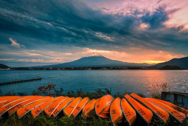 Mt. fuji über see kawaguchiko mit booten bei sonnenuntergang in fujikawaguchiko, japan.