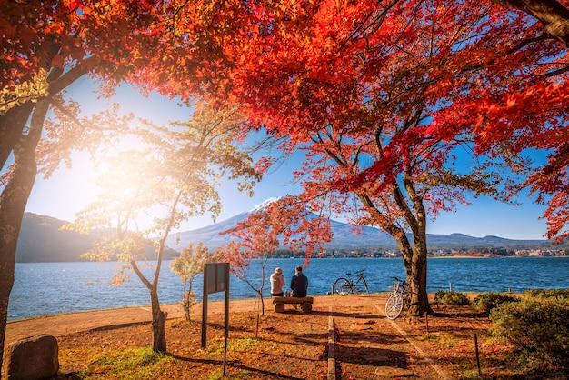 Mt. fuji über see kawaguchiko mit herbstlaub und paar lieben bei sonnenaufgang in japan.