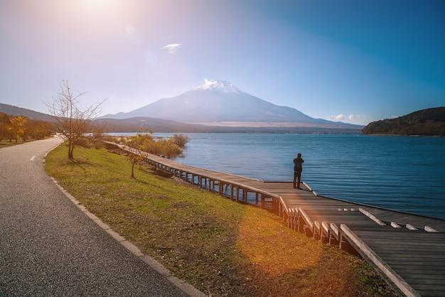 Mt. fuji über see kawaguchiko mit herbstlaub und reisendfrau bei sonnenaufgang in fujikawaguchiko, japan.