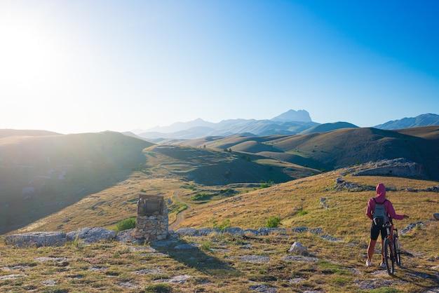 Mtb in den bergen der region abruzzen, gran sasso, appennino, italien. frau radfahren in grüner landschaft einzigartige berge landschaft sonne platzte hintergrundbeleuchtung. sommeraktivitäten im freien.