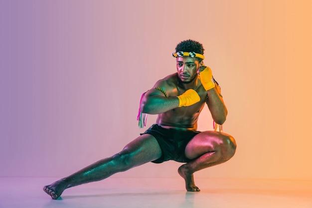 Muay thai. junger mann, der thailändisches boxen auf gradientenhintergrund im neonlicht ausübt.