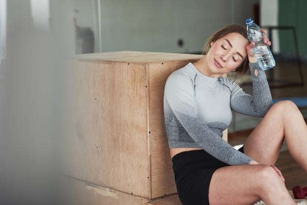 Müde aber glücklich. sportliche junge frau haben fitness-tag im fitnessstudio zur morgenzeit