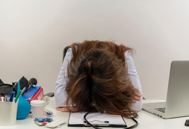 Müde ärztin mittleren alters, die medizinische robe und stethoskop trägt, die am schreibtisch mit zwischenablage der medizinischen werkzeuge und laptop sitzen, die kopf auf schreibtisch isoliert setzen