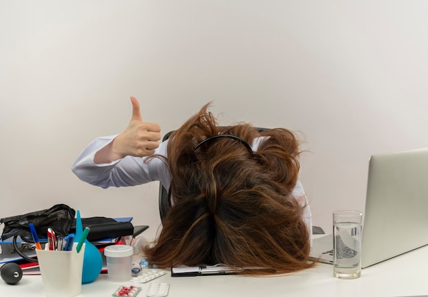 Müde ärztin mittleren alters in medizinischer robe und stethoskop, die am schreibtisch mit zwischenablage für medizinische werkzeuge und laptop sitzt und den kopf auf den schreibtisch legt und den daumen oben isoliert zeigt