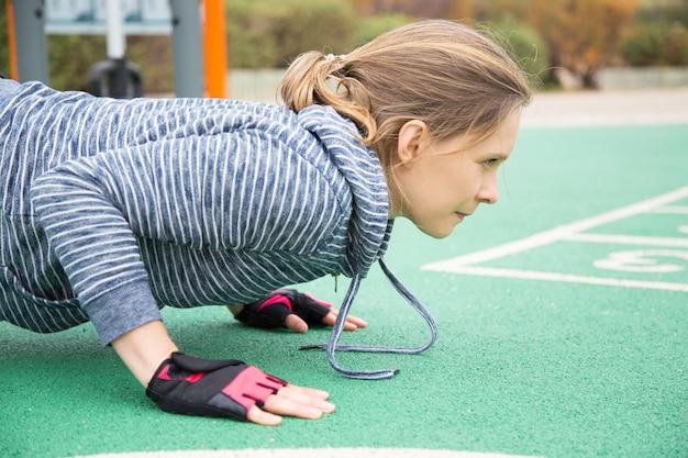 Müde angespannte athlet, die planke hält