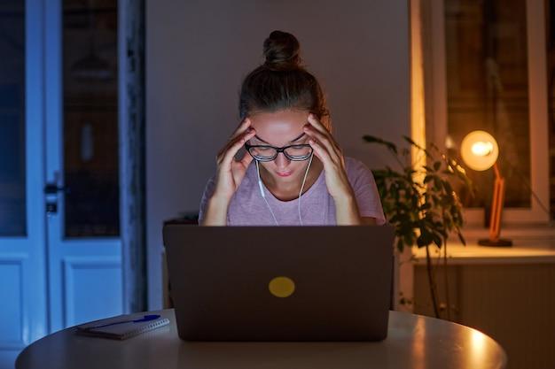 Müde angst betonte frau workaholic, die unter kopfschmerzen leidet, während sitzende späte computerarbeit