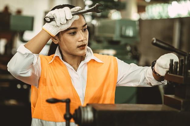 Müde arbeiterin asiatische arbeit harte arbeit in heißer fabrik, die schweiß wegwischt, der mit metallmaschine arbeitet.