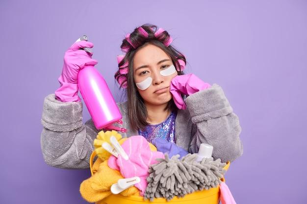 Müde asiatische haushälterin schaut traurig in die kamera, fühlt sich erschöpft, nachdem sie das haus gereinigt hat wendet lockenwickler auf das haar trägt schönheitspflaster trägt morgenmantel trägt waschmittel