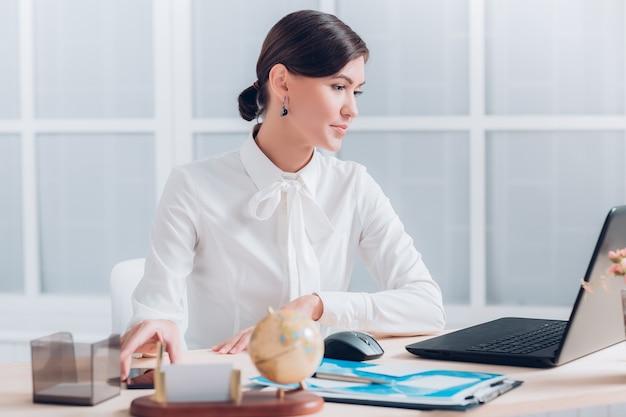 Müde attraktive geschäftsfrau, die am schreibtisch im büro arbeitet