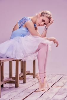 Müde balletttänzerin sitzt auf dem holzboden