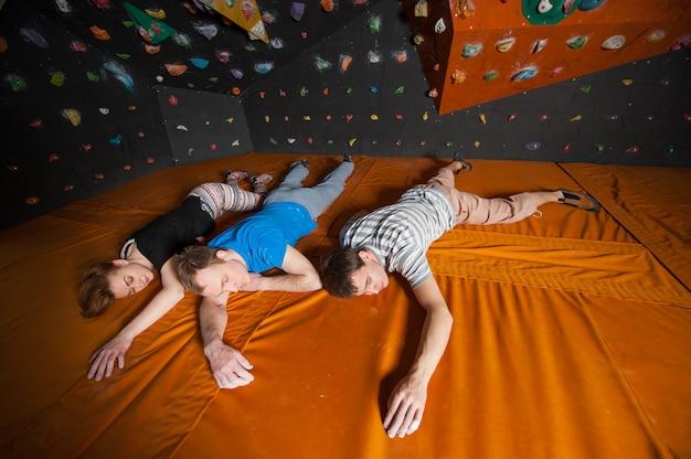 Müde bergsteiger mit geschlossenen augen, die zuhause nahe felsenwand liegen
