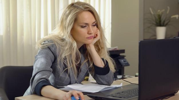 Müde blonde frau schläft am arbeitsplatz im büro ein. Premium Fotos