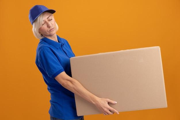 Müde blonde lieferfrau mittleren alters in blauer uniform und mütze, die in der profilansicht steht und karton mit geschlossenen augen isoliert auf oranger wand hält