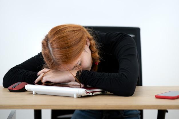 Müde büroangestellte frau, die ein nickerchen hinter dem schreibtisch hat.