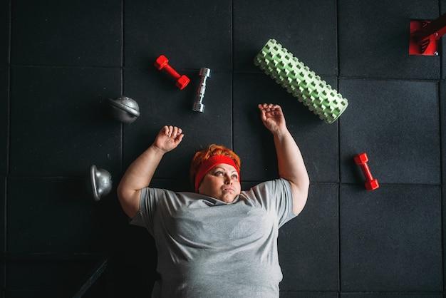 Müde dicke frau liegt auf dem boden im fitnessstudio. kalorien brennende, fettleibige weibliche person im sportverein