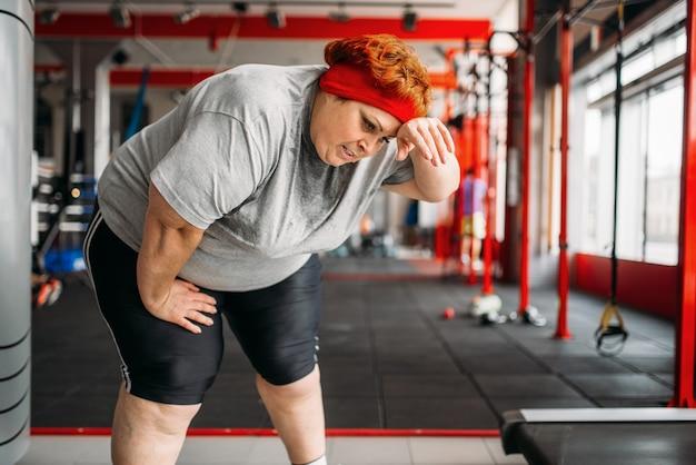 Müde dicke frau nach aktivem training im fitnessstudio. kalorien brennende, fettleibige weibliche person im sportverein