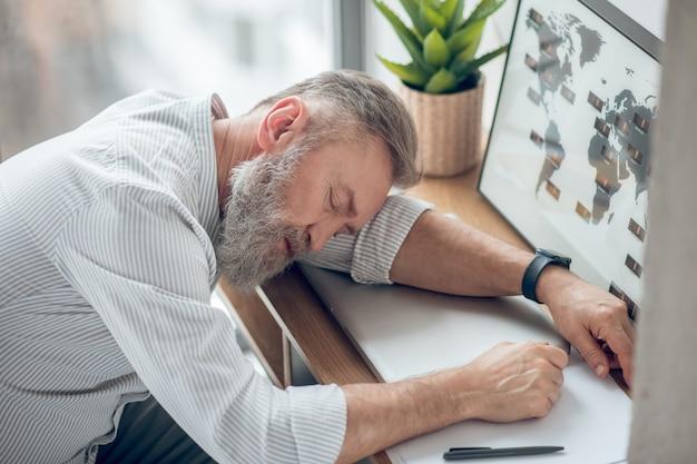 Müde. ein mann schläft am arbeitsplatz und fühlt sich müde