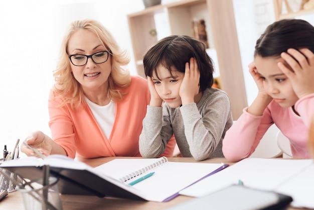 Müde enkelkinder, die hausaufgaben mit großmutter machen