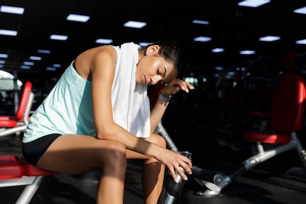 Müde erfreute sportlerin, die sich mit geschlossenen augen entspannt, während sie auf bank im fitnessstudio sitzt