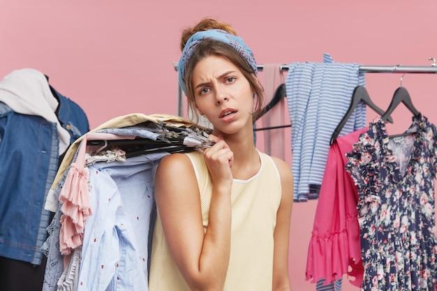 Müde, erschöpfte frau beim einkaufen, kleiderstapel auf kleiderbügeln halten, den ganzen tag in boutiquen und bekleidungsgeschäften verbringen, während sie versucht, das outfit für die party auszuwählen. beschäftigte käuferin