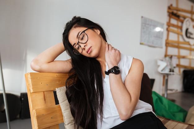 Müde erschöpfte frau in gläsern sitzen und entspannen