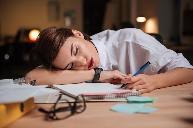 Müde erschöpfte junge geschäftsfrau, die am arbeitsplatz im büro schläft