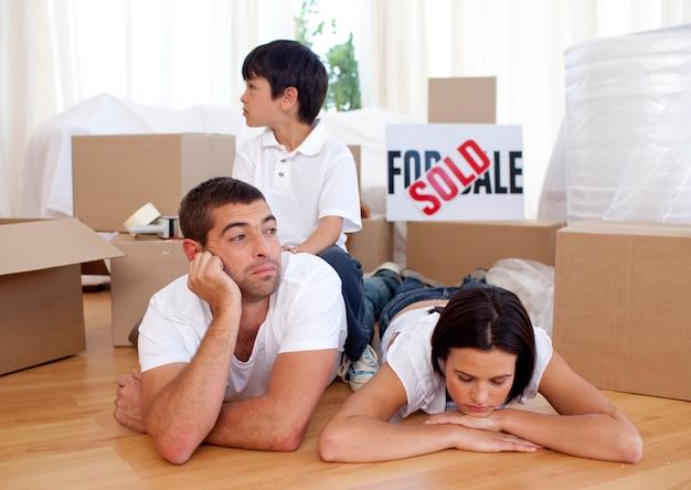 Müde familie, die auf fußboden sich entspannt, nachdem neues haus gekauft worden ist