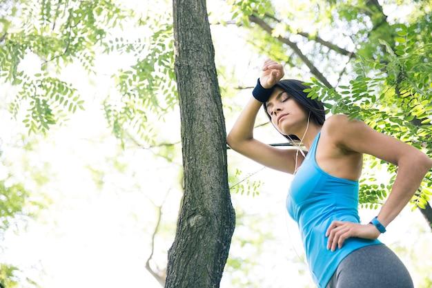 Müde fitnessfrau, die draußen ruht