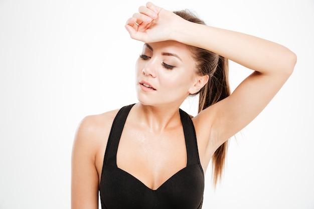 Müde fitnessfrau wischt sich nach dem training isoliert den schweiß von der stirn