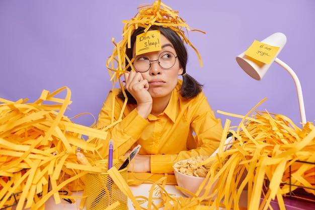 Müde, fleißiger student bereitet sich auf die prüfungssitzung vor, sitzt am desktop mit nachdenklichem ausdruck, umgeben von stapeln von geschnittenem papier, macht notizen auf aufklebern, um notwendige aufgaben nicht zu vergessen