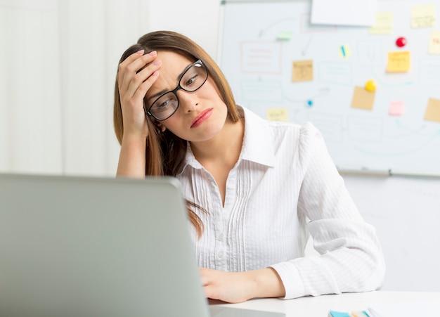 Müde frau bei der arbeit am computer. kopfschmerzen.