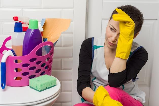 Müde frau, die auf badezimmerboden sitzt