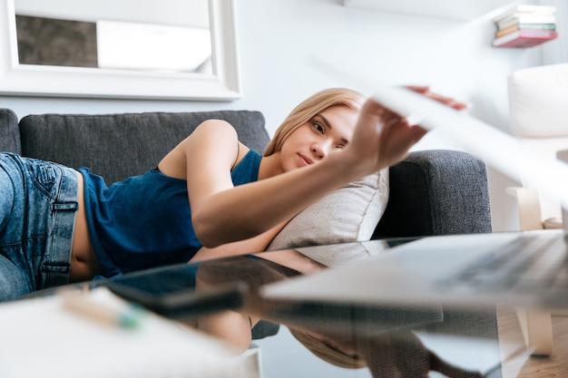 Müde frau, die auf sofa liegt und laptop zu hause schließt