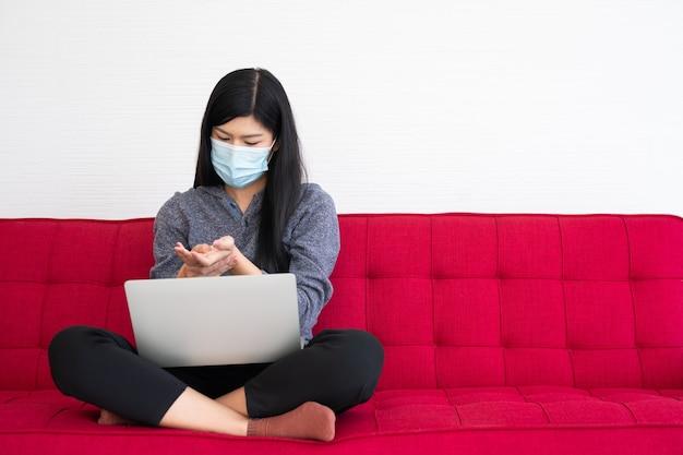 Müde frau, die eine gesichtsmaske trägt, verspannte muskeln im handgelenk, das leiden des bürosyndroms nach stundenlanger arbeit am computer. bürosyndrom und gesundheitskonzept.