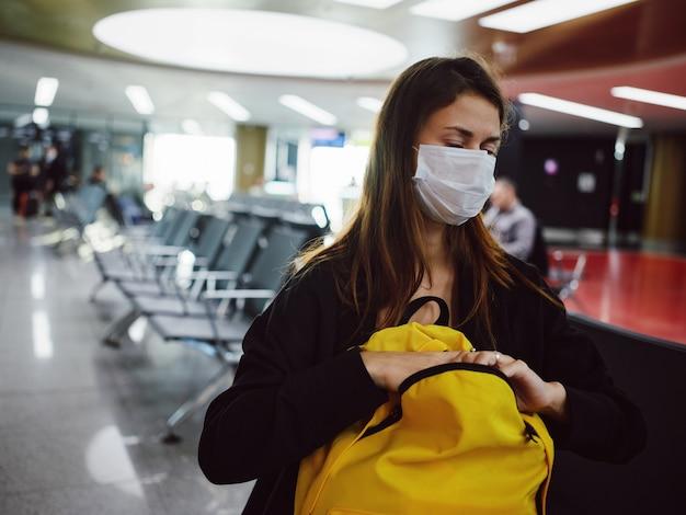 Müde frau, die eine medizinische maske trägt, hat den gelben rucksack des flughafens geschlossen. foto in hoher qualität