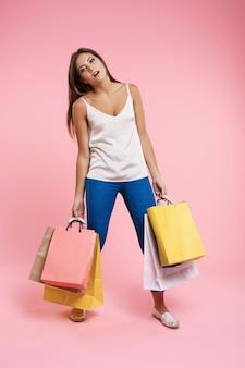 Müde frau, die einkaufstaschen nach langem tag im einkaufszentrum hält