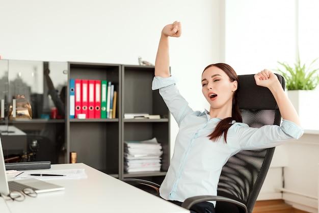 Müde frau, die im büro an ihrem arbeitsplatz gähnt