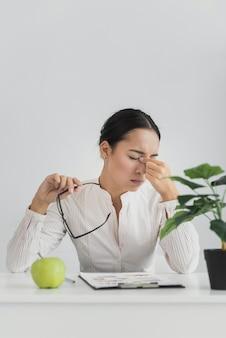 Müde frau, die im büro sitzt