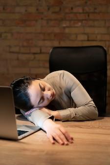 Müde frau, die spät für ein projekt arbeitet