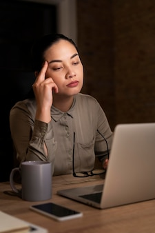 Müde frau, die spät im büro arbeitet