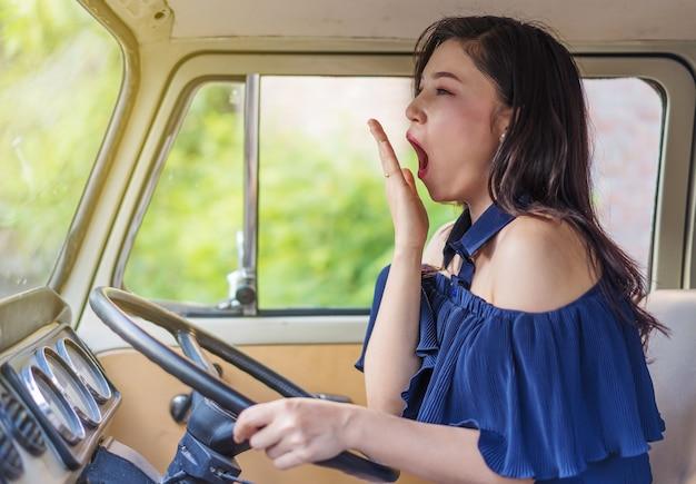 Müde frau, die weinleseauto fährt und gähnt