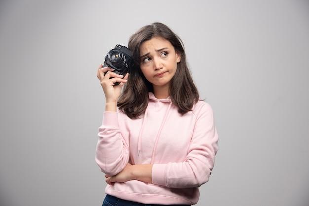 Müde frau im rosa sweatshirt, das kamera hält.