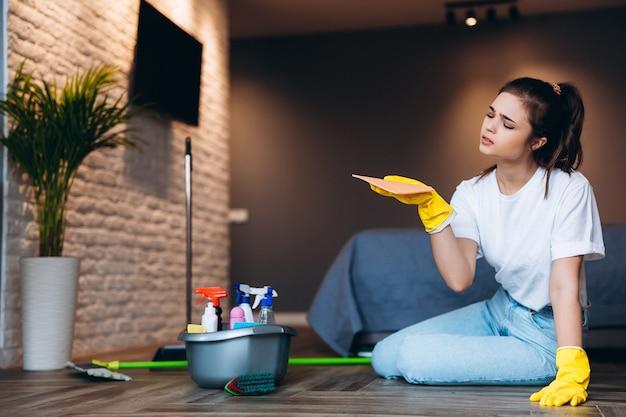 Müde frau im weißen t-shirt mit dunkler haarreinigung in gelben gummihandschuhen für handschutz und eimer mit reinigungsmitteln zu hause