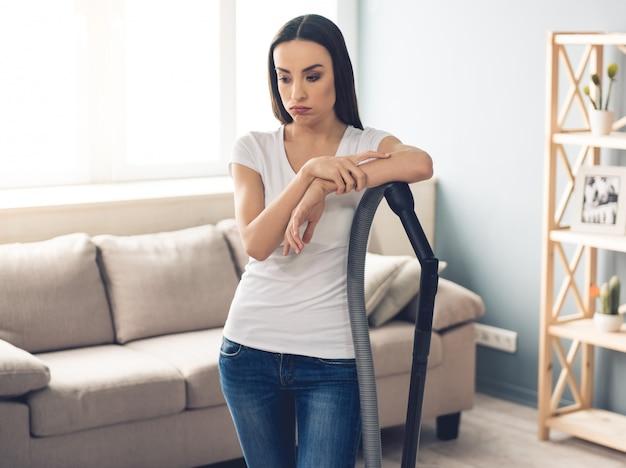 Müde frau in jeans benutzt einen staubsauger.