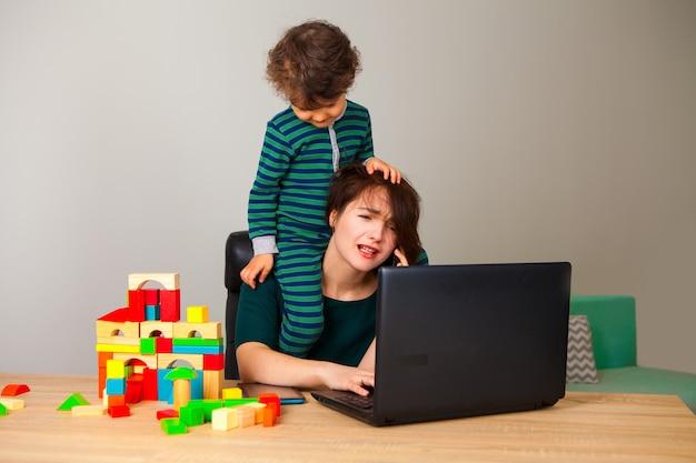 Müde frau mit einem kind am hals, das an einem computer sitzt und mit dem arbeitgeber telefoniert, während das kind würfel spielt und um sie herum hängt. unfähigkeit, zu hause zu arbeiten.