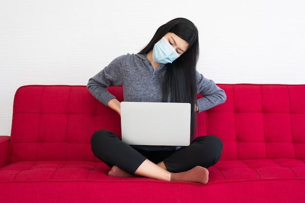 Müde frau mit gesichtsmaske und rückenschmerzen, das leiden des bürosyndroms nach stundenlanger arbeit am computer. bürosyndrom und gesundheitskonzept.