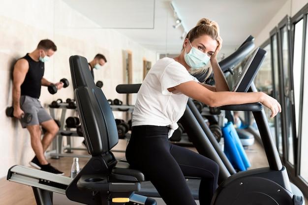 Müde frau mit medizinischer maske im fitnessstudio