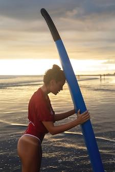 Müde frau nach harter surf-sitzung am strand zur sonnenuntergangszeit